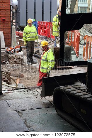 PORTSMOUTH, ENGLAND, 23RD MARCH 2016: Ground workers digging a trench for electric cables with the aid of a mechanical digger in portsmouth, england, 23rd march 2016