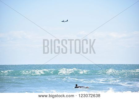 Surfer Paddles Out as Plane Flies Over Blue Sky Horizon