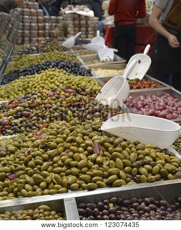 A stall selling olives on an Italian market stall. Focus on the foreground green olives.
