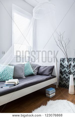 Modern decor of room with small white single bed with colorful pillows