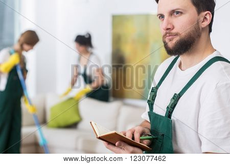 Young handsome cleaning man in uniform planning new job
