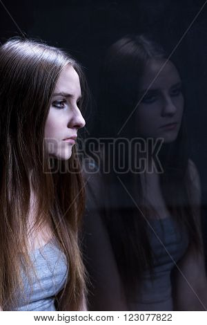 Depressed young girl addicted to tough drugs. Sitting alone in dark room
