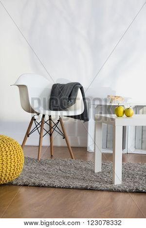 Rest corner in modern lounge with white armchair and coffee table