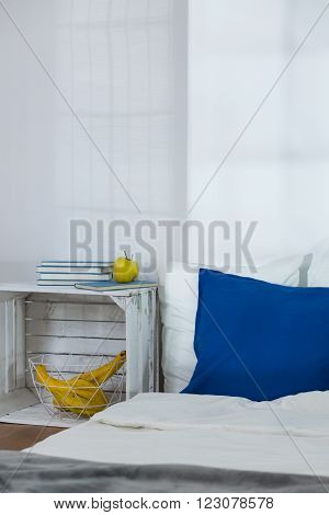 Simple cozy bedroom with white walls and mattress on floor. Stylish modern nightstand made of wooden box