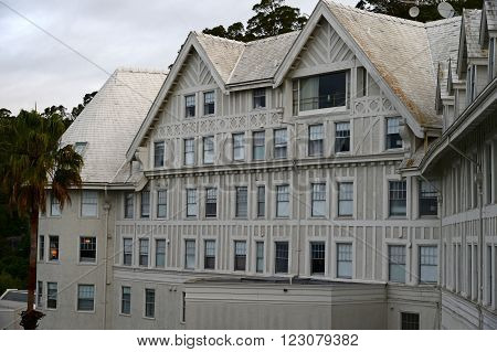 A stately old hotel is situated at the top of a hill giving occupants a magnificent view.