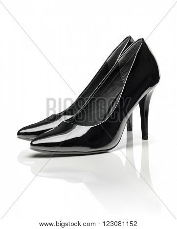 Black shiny patent leather stiletto heel pumps isolated on white with natural reflection.
