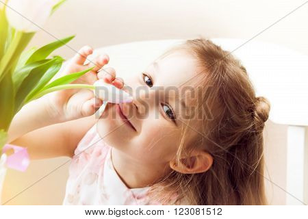 Happy  smiling child smelling flower. She is holding tulip blossom in her hands. Bright back light.
