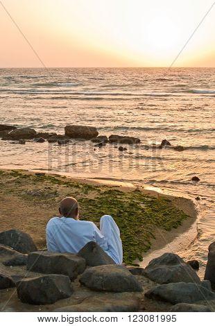 Jeddah, Saudi Arabia - November 19 2008: A local old man  looking at the sea on the Corniche at the sunset. ** Note: Visible grain at 100%, best at smaller sizes