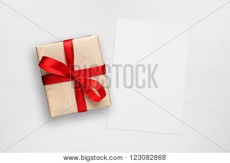 Gift box and greeting card on white wooden table