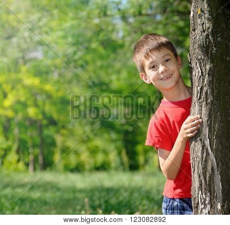 Cute boy standing near tree in park