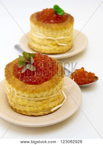 Tartlets with red caviar close up. Snack with red caviar tartlet on  plate isolated on white background.