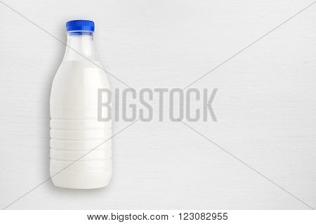 Milk bottle on white wooden table top view