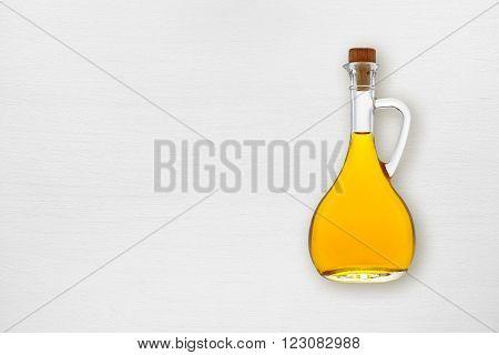Olive oil bottle on white wooden table