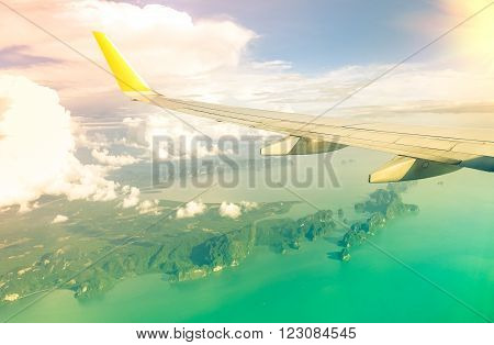 Airplane window view on wing with green ocean background - Aerial panorama of tropical islands with sun light colors - Colorful vintage filter look focus on aircraft wing