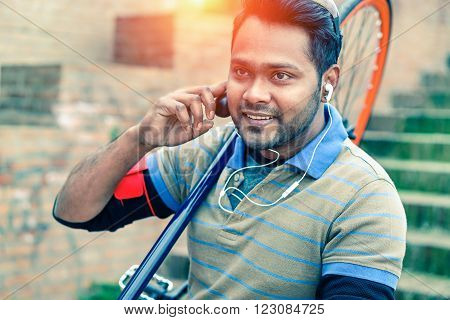 Young indian man carrying bike down old urban steps - Cheerful asian guy with earphone and sport bicycle going to work - Concept of green alternative transportation and using mobile technology