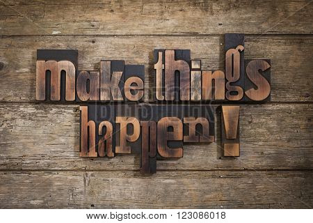 make things happen, phrase set with vintage letterpress printing blocks on rustic wooden background