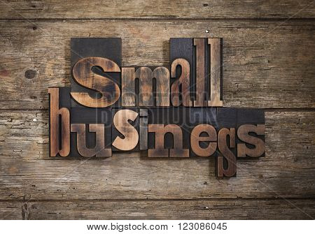 small business, phrase set with vintage letterpress printing blocks on rustic wooden background