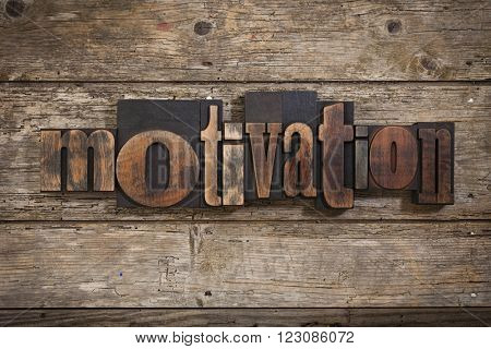 motivation, single word set with vintage letterpress printing blocks on rustic wooden background