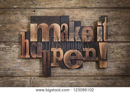 make it happen, phrase set with vintage letterpress printing blocks on rustic wooden background
