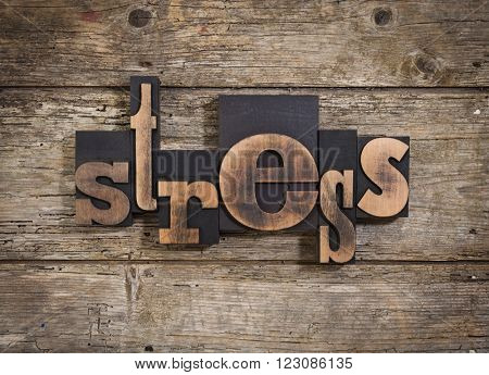 stress, single word set with vintage letterpress printing blocks on rustic wooden background