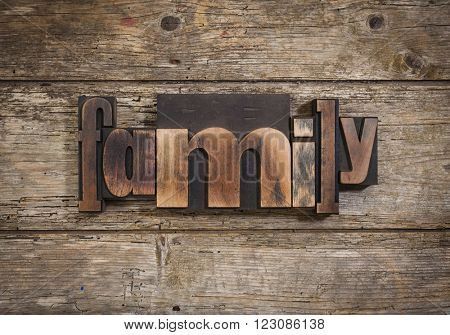 family, single word set with vintage letterpress printing blocks on rustic wooden background
