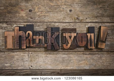 thank you, phrase set with vintage letterpress printing blocks on rustic wooden background