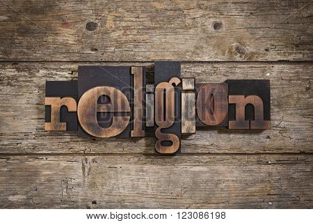 religion, single word set with vintage letterpress printing blocks on rustic wooden background