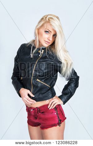 Portrait of a sexy young woman in leather jacket and red shorts. Isolated on solid background