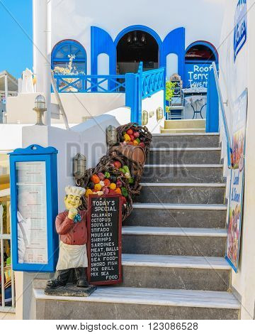 THIRA, SANTORINI, GREECE - AUGUST 25, 2015: Entrance to traditional Greek tavern , decorated with vegetables and figure of cook