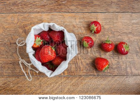 Overhead view of fresh strawberries in a small hessian bag on a wooden kitchen table with a small group of strawberries beside the bag.
