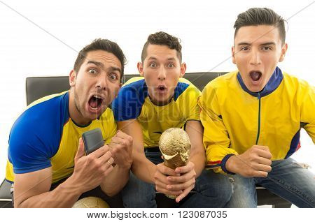 Three friends sitting on sofa wearing yellow sports shirts screaming cheering at camera with enthusiasm, white background, shot from above.