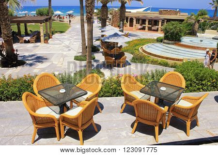 CRETE, GREECE - JULY 23, 2015: Summer view with mediterranean hotel resort and al fresco wicker seats on the terrace, Crete, Greece