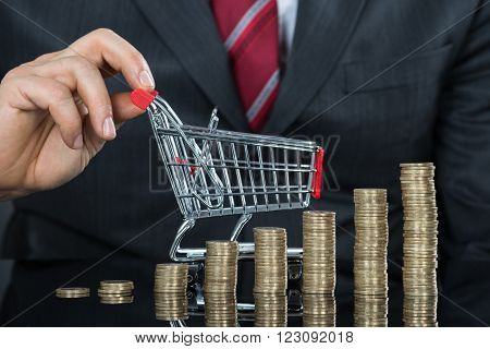 Close-up Of Businessman With Stack Of Coins And Shopping Cart