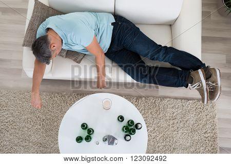 Man Taking A Nap On Sofa At Home