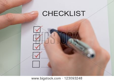 Close-up Of Woman Marking On Checklist Form With Red Pen