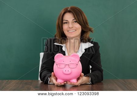 Happy Female Teacher Holding Piggybank In Classroom