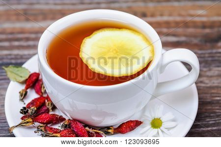 Tea with wild rose and lemon in a white cup