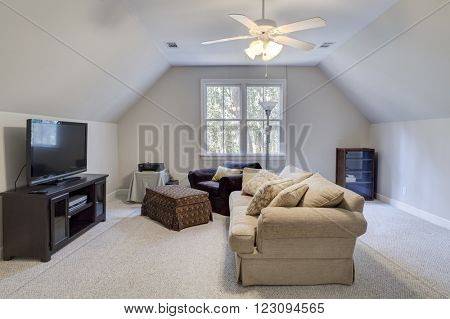 Attic man cave with furniture and flat screen tv