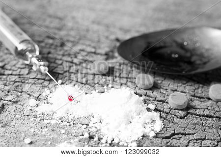 Hand injection drug  with old glass syringe blood, amphetamine tablets and cooked heroin in spoon. on old wood background