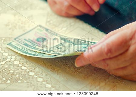 Closeup of senior lady with dollar bills in hands, toned image instagram-like color, selective focus, very shallow DOF.