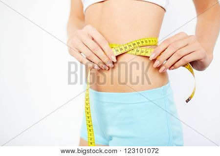 Close-up of woman measuring her waist