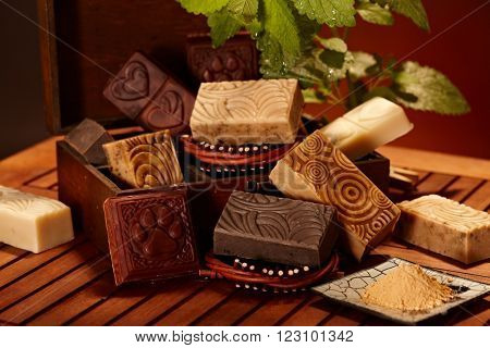 Variety of hand made natural soap bars arranged in wooden box.