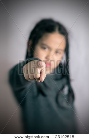angry Cute little asian girl pointing the finger at camera ,focus at her finger