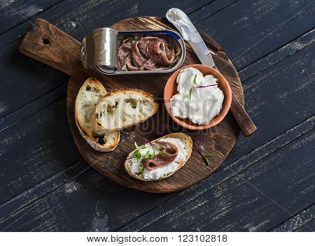 Anchovy and goat cheese sandwich on rustic wooden board on dark wooden background