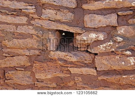 Up close detail of adobe brick wall of an ancient Indian pueblo ruin in Arizona with opening