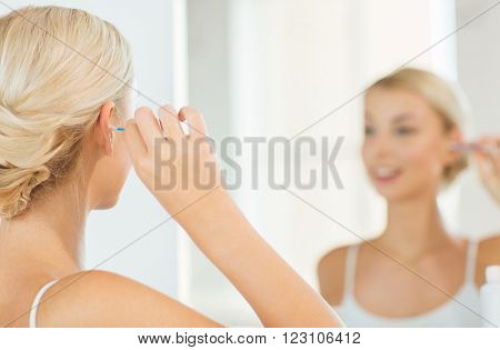 beauty, hygiene and people concept - close up of smiling young woman cleaning ear with cotton swab and looking to mirror at home bathroom