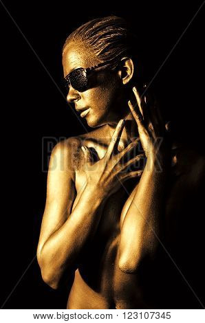 Beautiful naked young woman in gold with sunglasses.