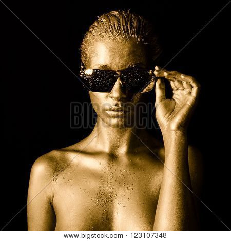 Head portrait of a beautiful young woman in gold with sunglasses.