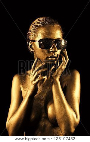 Beautiful young naked woman in gold and sunglasses