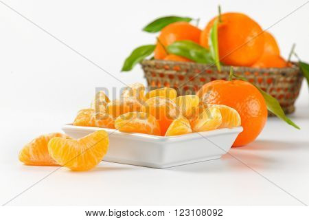 bowl of tangerine segments and whole tangerines on white background